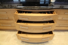 Curved oak pan drawers under induction hob