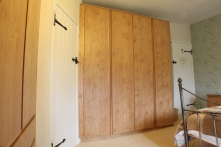 Floor to ceiling wardrobes maximise storage in this cottage bedroom